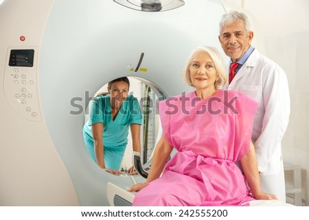 Woman in 60s ready to undergo MRi scan, assisted by two reassuring doctors. - stock photo