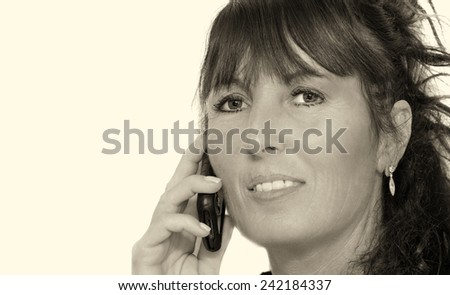 Woman in 50s speaking at mobile phone and smiling. Isolated on white.