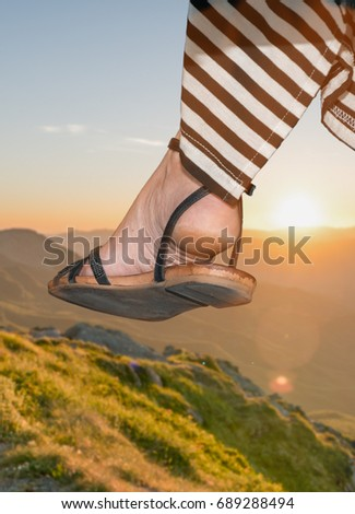 Woman in sandals flat in a sunset