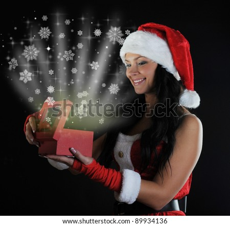 Woman  in Santa Claus hat smiles and holding a gift in magic packing  on a dark background - stock photo