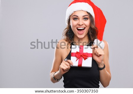 Woman in Santa hat holding gifts, isolated on gray