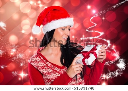 Woman in santa hat looking at christmas gift against digitally generated background during christmas time