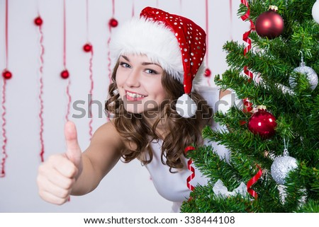 woman in santa hat thumbs up near decorated Christmas tree - stock photo