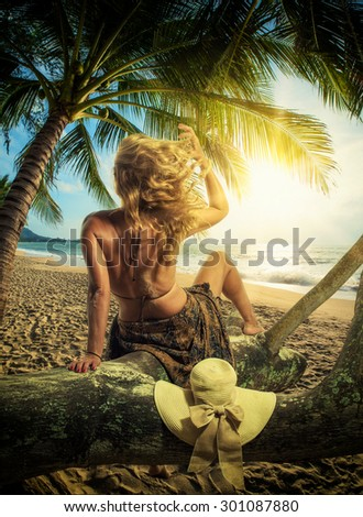 Woman in sarong on the beach at sunrise in Thailand - stock photo