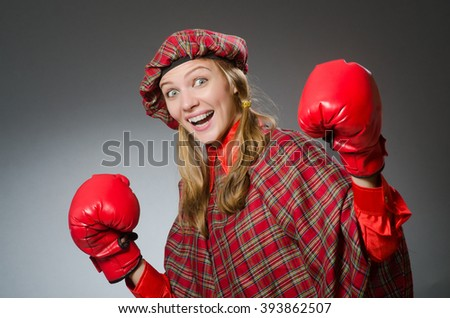 Woman in scottish clothing in boxing concept