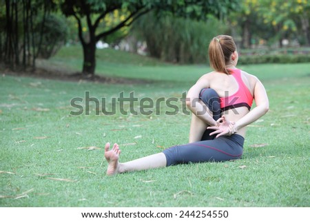 Woman in Seated Twist Yoga Pose on lawn - stock photo