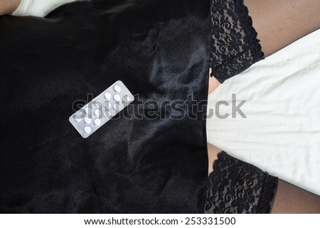 Woman in sexy dress lying on the bed with drugs - stock photo