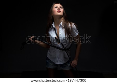 Woman in shadow with whip - isolated photo