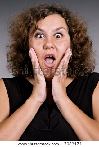 woman in shock over grey background - stock photo