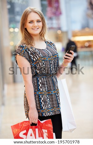 Woman In Shopping Mall Using Mobile Phone - stock photo