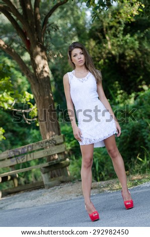 Woman in short white dress and red high heels, lush vegetation as background