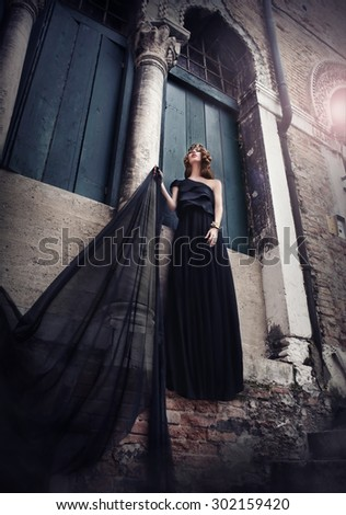 Woman in silk black dress at old building...  - stock photo