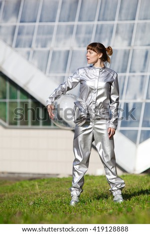 Woman in silver astronaut costume standing on the grass and looking away - stock photo
