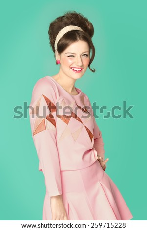 Woman in sixties style fashion posing with wink. Pink and cyan retro colors. Sixties hairstyle. - stock photo