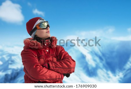 Woman in ski glasses looking away, mountains in the background - stock photo