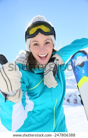 Woman in ski outfit standing at top of mountain - stock photo