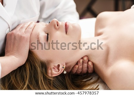 Woman in spa salon getting face treatment.