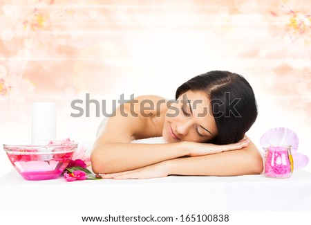 woman in spa salon lying on massage table, beauty girl closed eyes, body health care over flower background