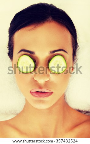 Woman in spa with cucumber on eyes.