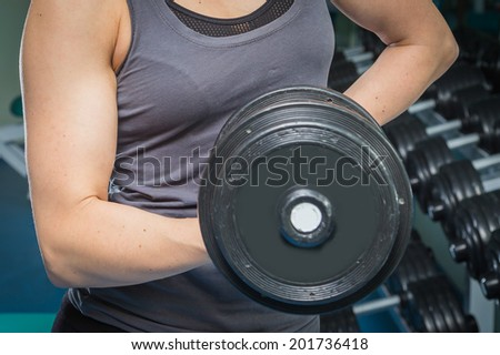 Woman in sport equipment practice with barbell