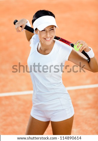 Woman in sports wear keeps tennis racket and ball on her shoulders at the clay tennis court. Competition - stock photo