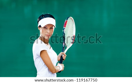 Woman in sportswear plays tennis at match - stock photo