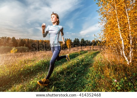 Woman in sportswear running along the path in autumn forest - stock photo