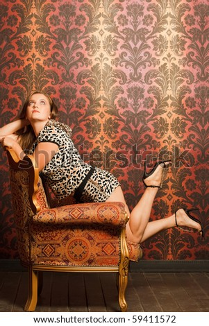 woman in spot cat clothes in  vintage chair looks up. red-yellow pattern wallpaper and wooden floor - stock photo