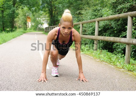 Woman in start position preparing to run