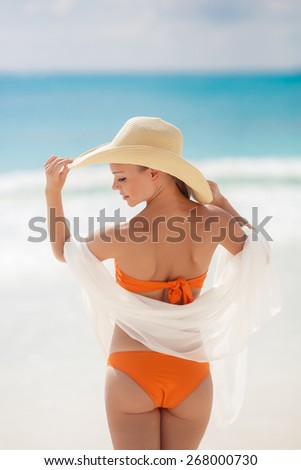 Woman in straw hat and orange bikini on a tropical beach. view of female back on a background of the ocean. Young woman in white walking on ocean beach - stock photo