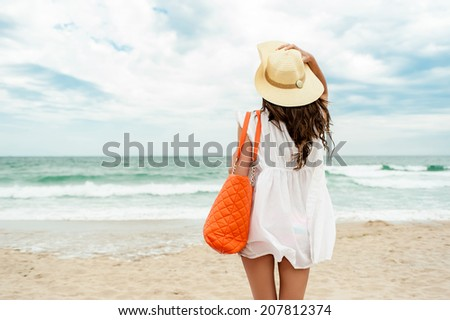 Woman in straw hat and white dress on a tropical beach with orange bag - stock photo