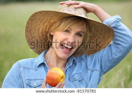 Woman in straw hat eating apple