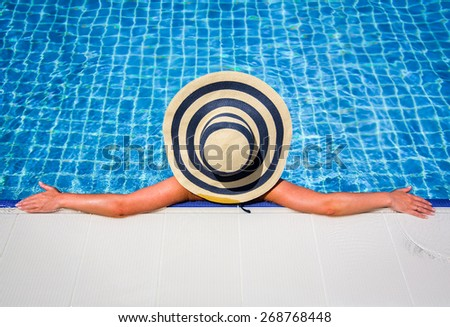 Woman in straw hat relaxing swimming pool. Bottom composition perfect copy space for your text ads. - stock photo