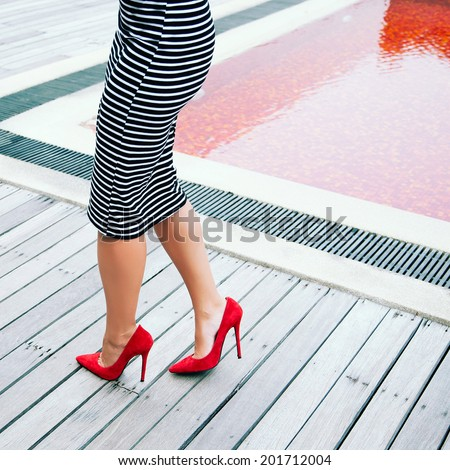 Woman in stripy black and white dress posing near creative red pool in height heeled classic pumps. Fashion image. - stock photo