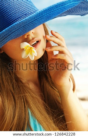 woman in stylish hat with balinese flower - stock photo