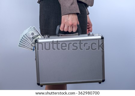 Woman in suit carries metal briefcase with dollars - stock photo