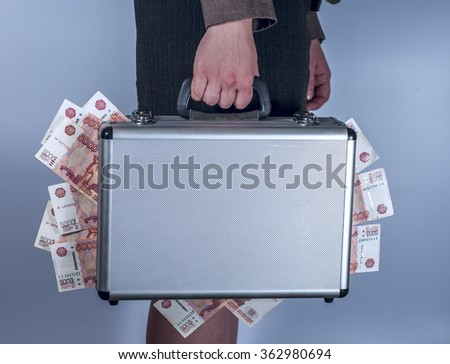 Woman in suit carries metal briefcase with rubles - stock photo