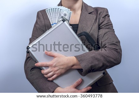 Woman in suit holds metal briefcase with dollars