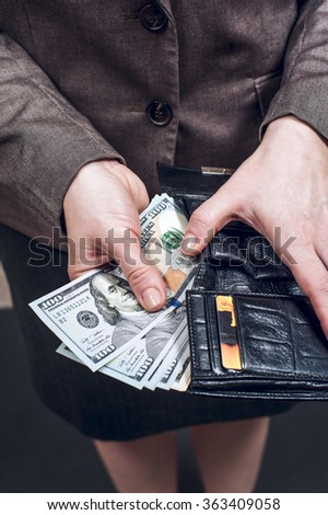 Woman in suit with leather wallet full of US dollars. Conception of safe storage and protection of cash. Financial theme.  - stock photo