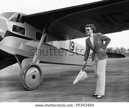 Woman in suit with plane - stock photo