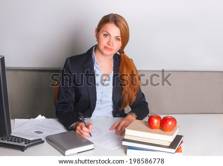 Woman in suit writing sitting at the table - stock photo