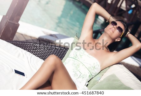 Woman in summer dress relaxing at luxury resort terrace, dreaming. Female relaxing on lounge chair. Vacations And Tourism Concept. - stock photo