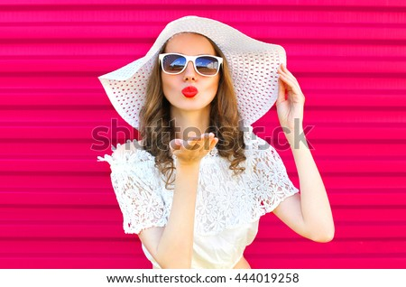 Woman in summer straw hat sends an air kiss over colorful pink background - stock photo