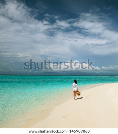 Woman in sun hat at tropical beach - stock photo