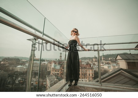 woman in sunglasses and black dress in the city