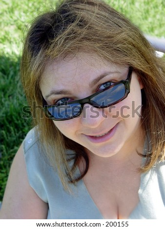 Woman in sunglasses on the grass - stock photo