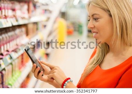 Woman in supermarket checking prices on her smartphone