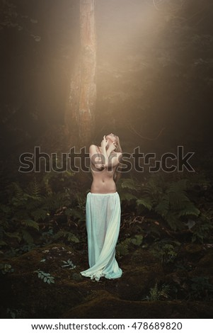 Woman in surreal forest looking at magical light from above. Fantasy