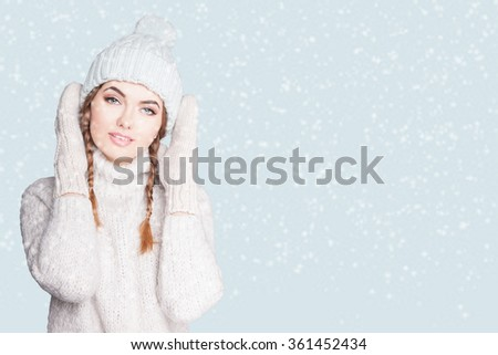 Woman in sweater and mittens.Woman in winter.Portrait of sensual woman enjoying snow. Wearing warm hat on a light background tender, girl looking at the camera.WARM knit women's clothes