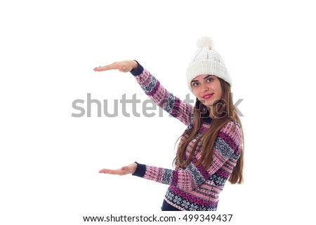 Woman in sweater and white hat holding something